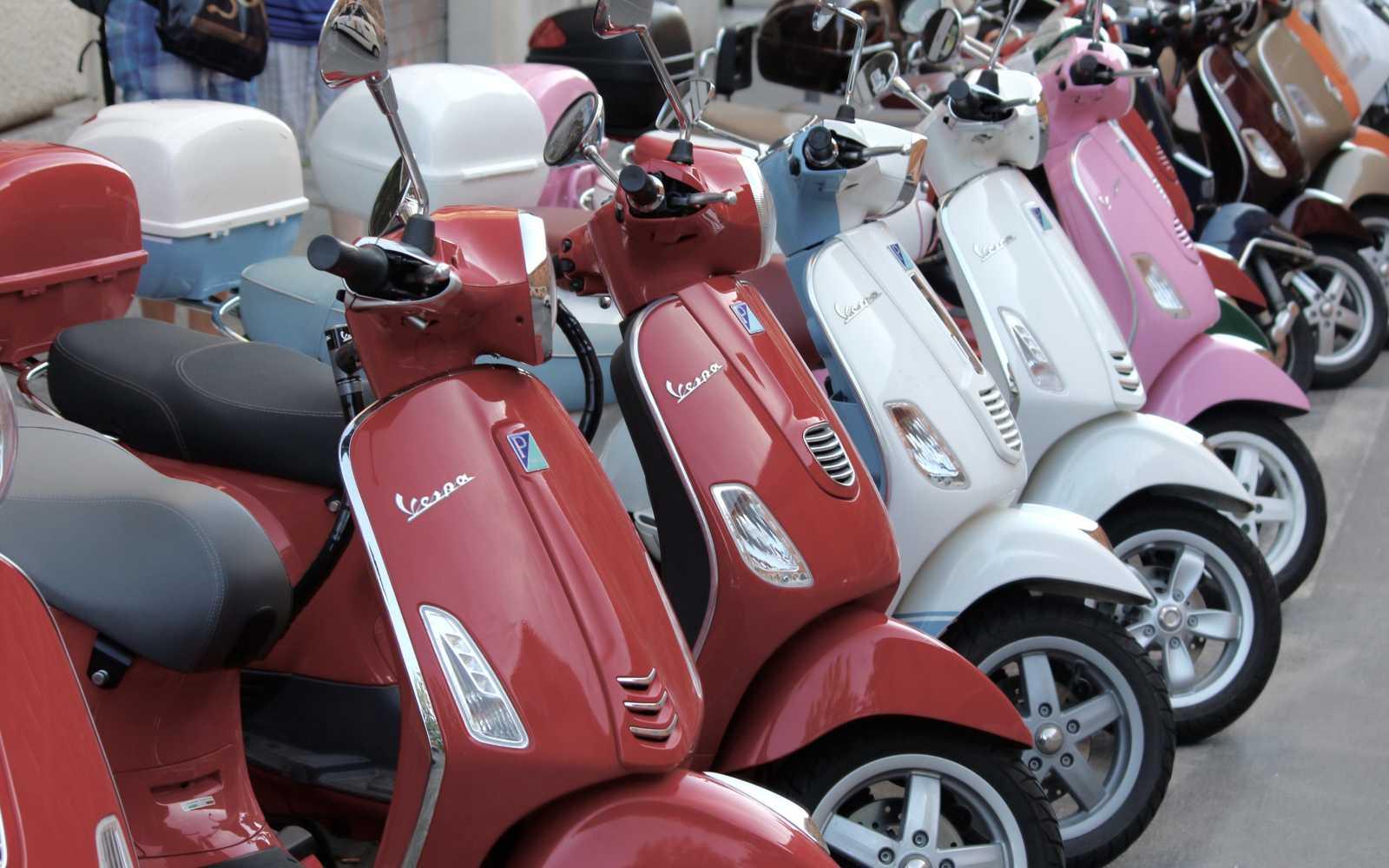 vespe rosse, bianche e rosa esposte a roma per noleggio
